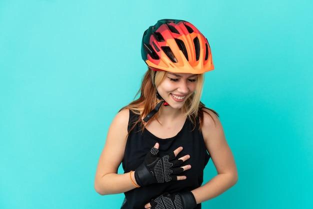 Молодой велосипедист девушка на изолированном синем фоне много улыбается