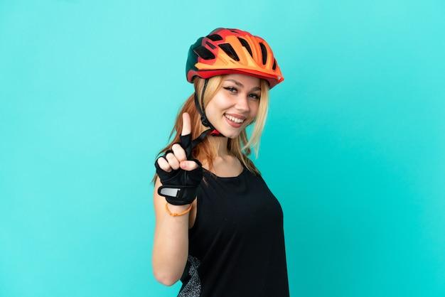 Молодой велосипедист девушка на изолированном синем фоне улыбается и показывает знак победы