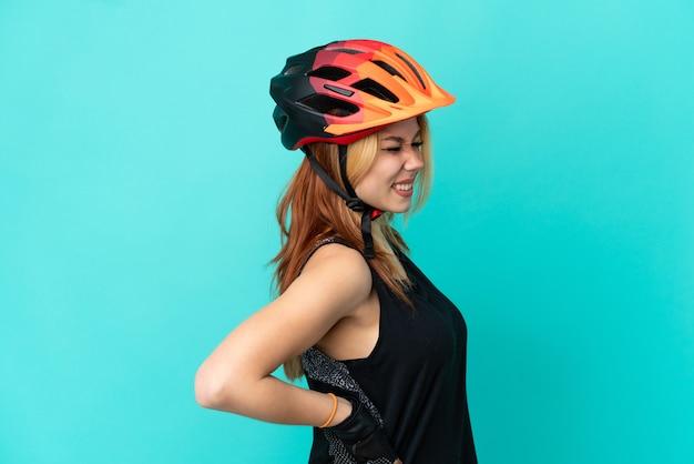 Молодая велосипедистка на изолированном синем фоне страдает от боли в спине из-за того, что приложила усилия Premium Фотографии