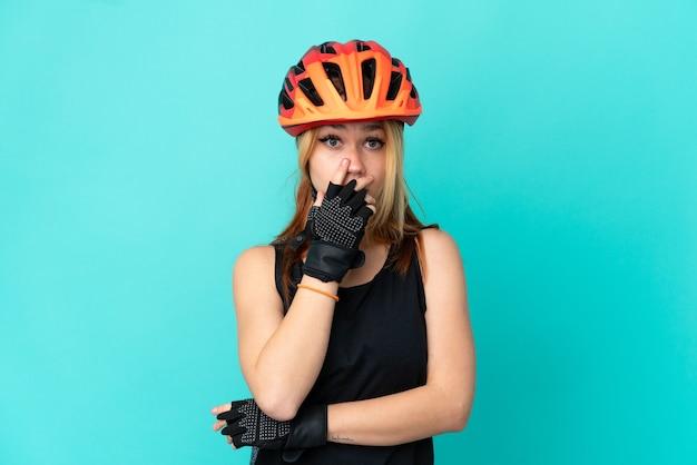 Молодая велосипедистка на изолированном синем фоне удивлена и шокирована, глядя вправо