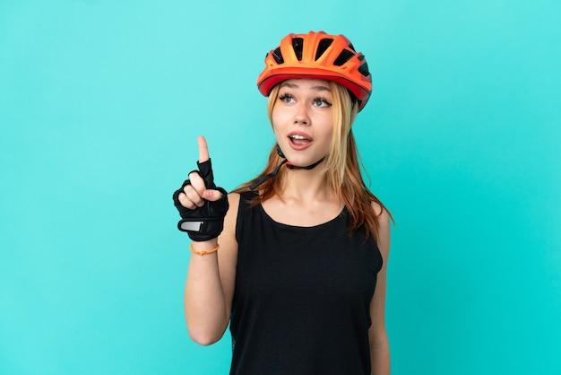 Молодая велосипедистка на изолированном синем фоне думает о идее, указывая пальцем вверх