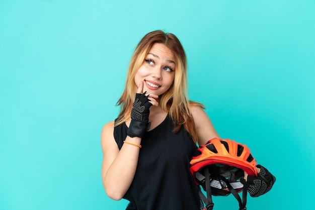 Молодая велосипедистка на изолированном синем фоне думает об идее, глядя вверх