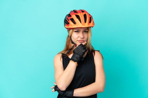 Девушка молодой велосипедист на изолированном синем фоне и мышления