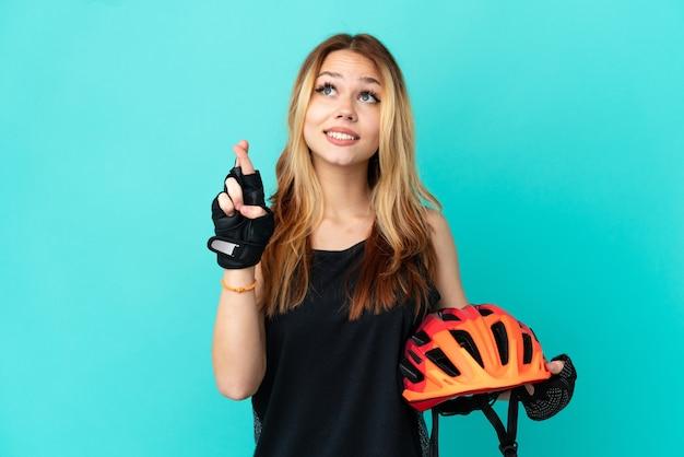 Молодая велосипедистка на изолированном синем фоне со скрещенными пальцами и желанием всего наилучшего