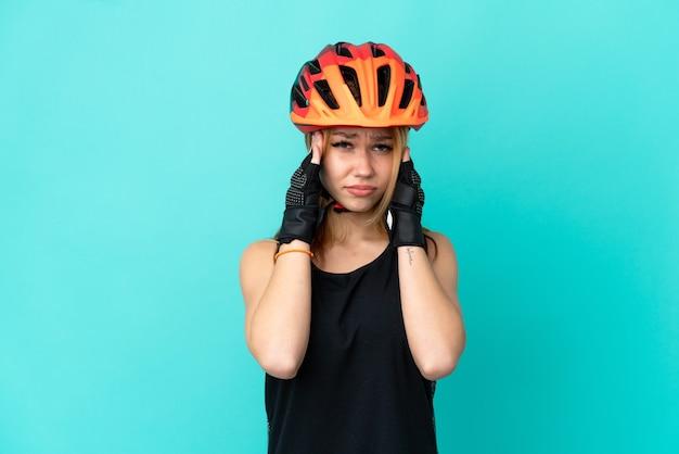 Девушка молодой велосипедист на изолированном синем фоне с головной болью