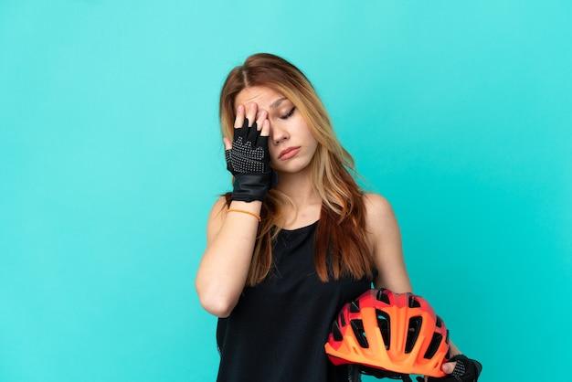 頭痛のある孤立した青い背景の上の若いサイクリストの女の子