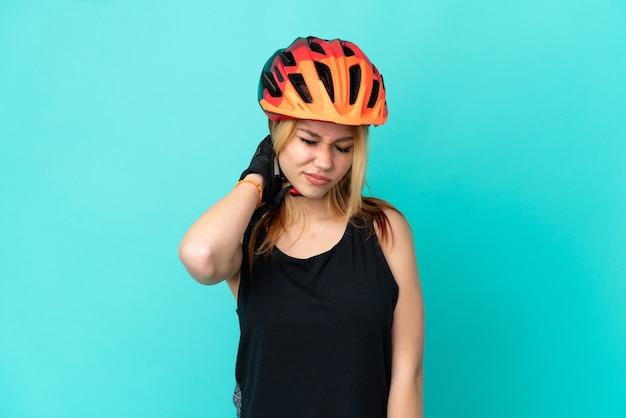 Молодая велосипедистка на изолированном синем фоне с болью в шее