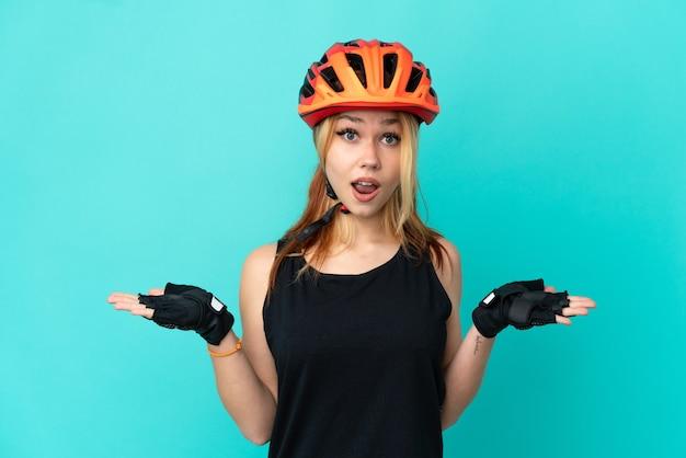 Молодая велосипедистка на изолированном синем фоне с шокированным выражением лица