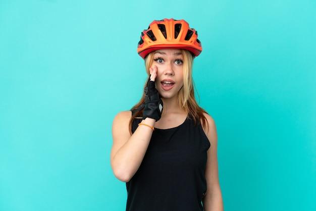 Молодая велосипедистка на изолированном синем фоне с удивлением и шокированным выражением лица Premium Фотографии