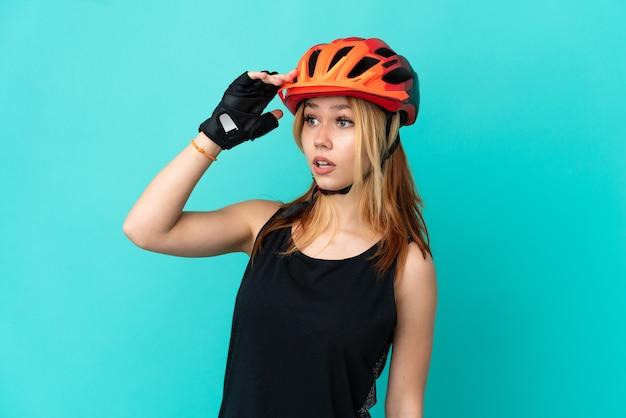 Молодая велосипедистка на изолированном синем фоне с удивленным выражением лица, глядя в сторону