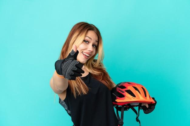 Молодая велосипедистка на изолированном синем фоне с большими пальцами руки вверх, потому что произошло что-то хорошее