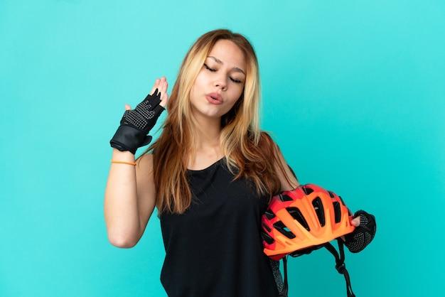 Молодая велосипедистка на изолированном синем фоне с усталым и больным выражением лица