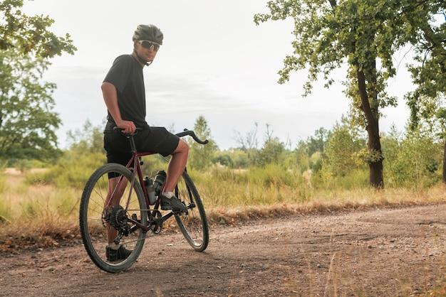 眼鏡とヘルメットをかぶった若いサイクリストが田舎の砂利道に自転車で立っています。