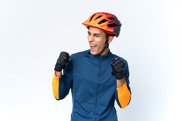 Изолированный молодой велосипедист празднует победу