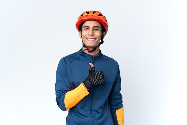 Молодой велосипедист человек изолирован на фоне, показывая большой палец вверх жест