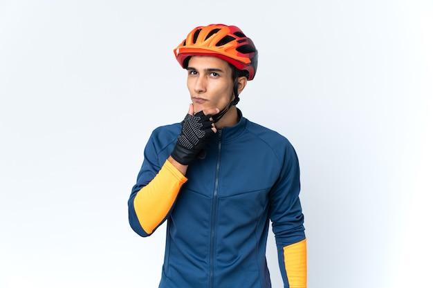 Молодой велосипедист человек изолирован на фоне сомнений Premium Фотографии