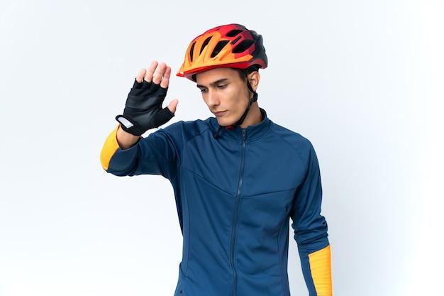 Молодой велосипедист человек изолирован на фоне, делая стоп-жест и разочарованный