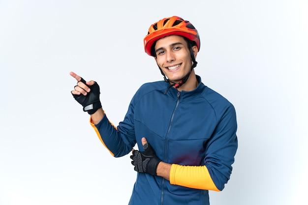 Молодой велосипедист человек изолирован на фоне указывая пальцем в сторону