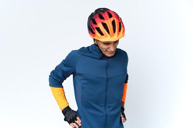 Молодой велосипедист человек изолирован на фоне страдает от боли в спине за то, что приложил усилие