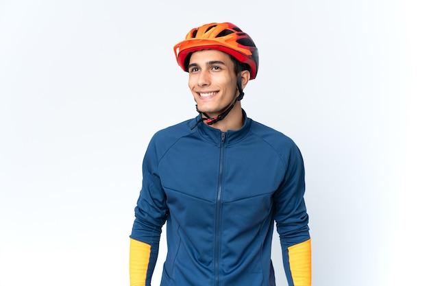 Молодой велосипедист человек изолирован на фоне, думая об идее, глядя вверх