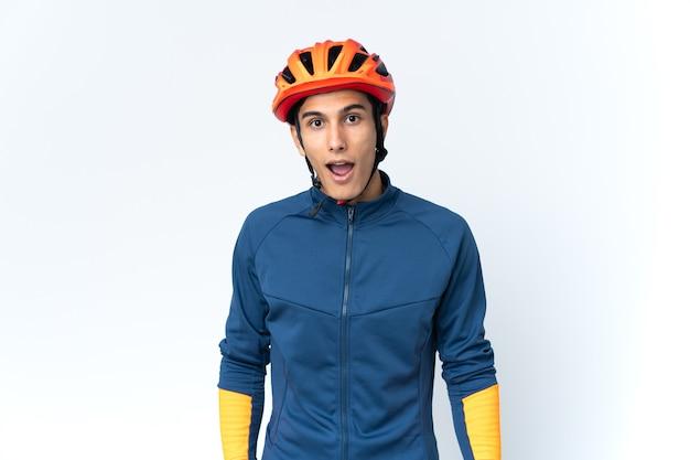 Молодой велосипедист мужчина изолирован на фоне с удивленным выражением лица