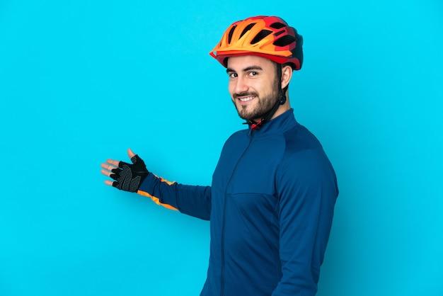 Молодой велосипедист мужчина изолирован на синем фоне, протягивая руки в сторону для приглашения приехать