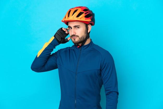 Молодой велосипедист человек, изолированные на синем фоне, сомневаясь