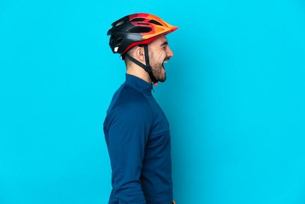 Молодой велосипедист мужчина изолирован на синем фоне, смеясь в боковом положении