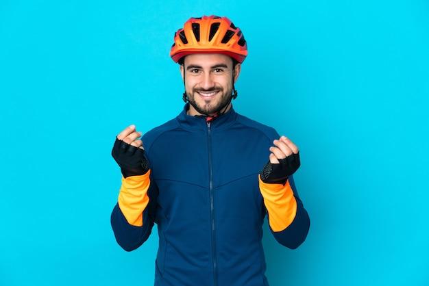 Молодой велосипедист человек изолирован на синем фоне, делая денежный жест