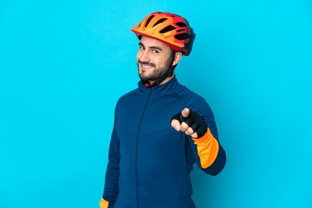 Молодой велосипедист человек изолирован на синем фоне, указывая вперед с счастливым выражением лица