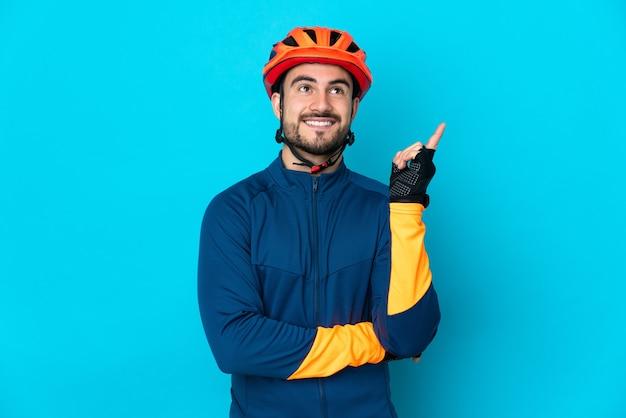 Молодой велосипедист мужчина изолирован на синем фоне, указывая вверх прекрасную идею