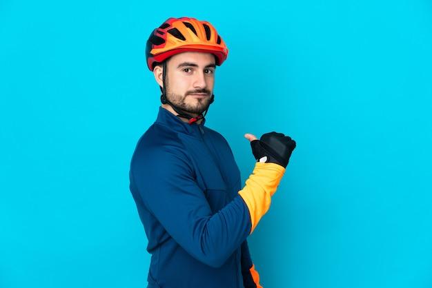 Молодой велосипедист мужчина изолирован на синем фоне, гордый и самодовольный