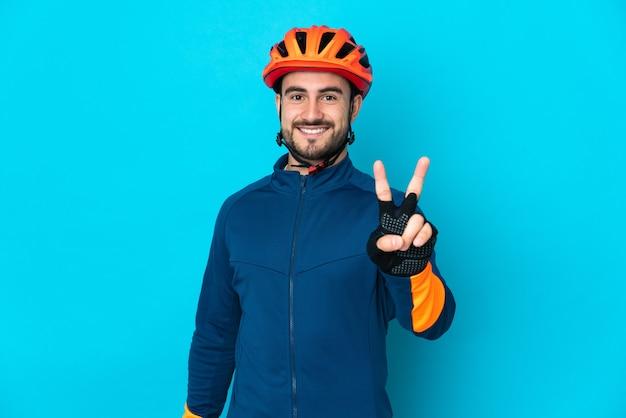 Молодой велосипедист человек изолирован на синем фоне улыбается и показывает знак победы