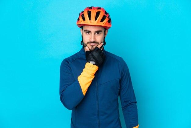 Молодой велосипедист человек изолирован на синем фоне мышления
