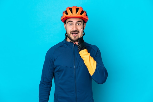 Молодой велосипедист изолирован на синем фоне с удивленным и шокированным выражением лица