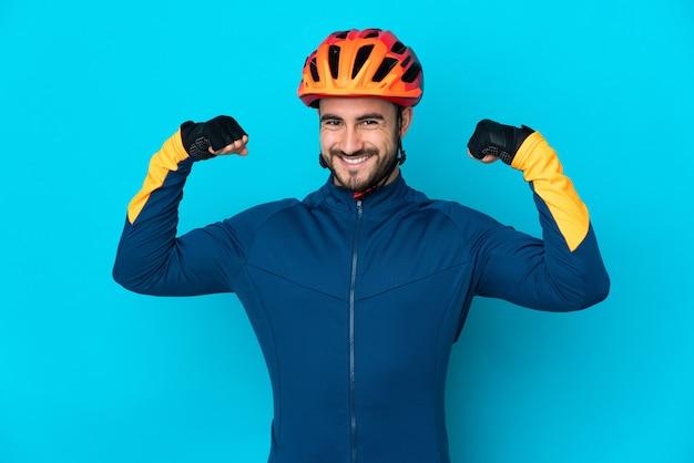 Молодой велосипедист мужчина изолирован на синей стене, делая сильный жест