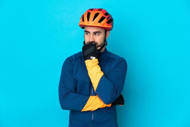 Молодой велосипедист человек изолирован на синей стене, сомневаясь