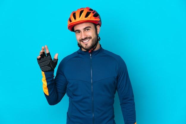 幸せな表情で手で敬礼青い壁に孤立した若いサイクリストの男