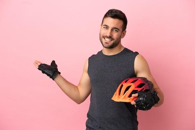 Молодой велосипедист мужчина изолирован на розовом фоне, протягивая руки в сторону для приглашения приехать