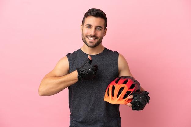 Молодой велосипедист мужчина изолирован на розовом фоне, показывая большой палец вверх жест