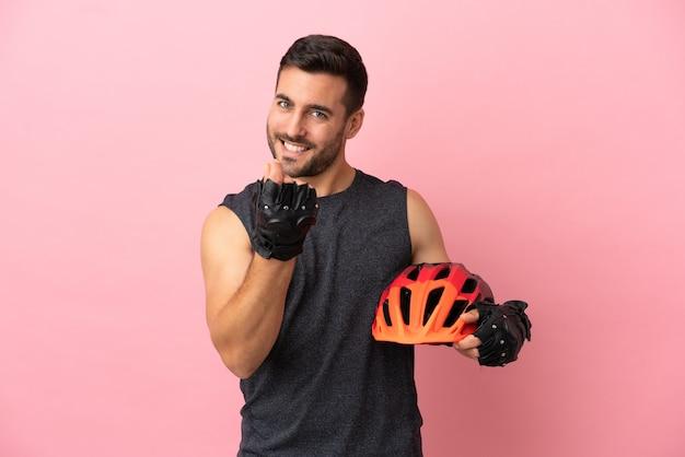 Молодой велосипедист человек изолирован на розовом фоне, делая денежный жест