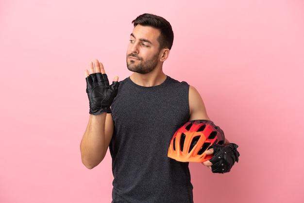 Молодой велосипедист мужчина изолирован на розовом фоне, делая жест стоп и разочарованный