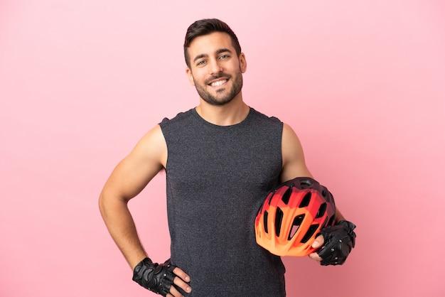 ピンクの背景に分離された若いサイクリストの男は、腰に腕と笑顔でポーズをとる