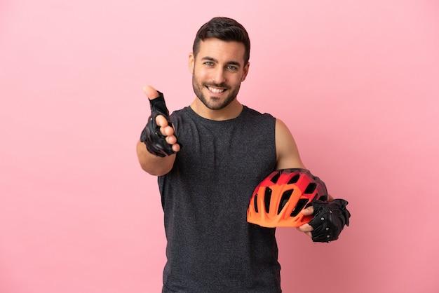 Молодой велосипедист мужчина изолирован на розовом фоне, пожимая руку для заключения хорошей сделки