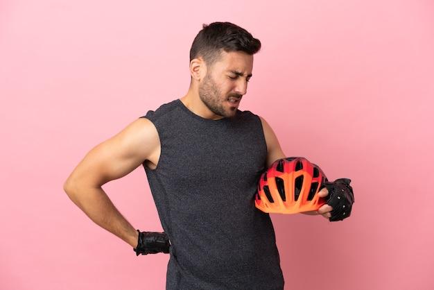努力したために腰痛に苦しんでピンクの背景に孤立した若いサイクリストの男