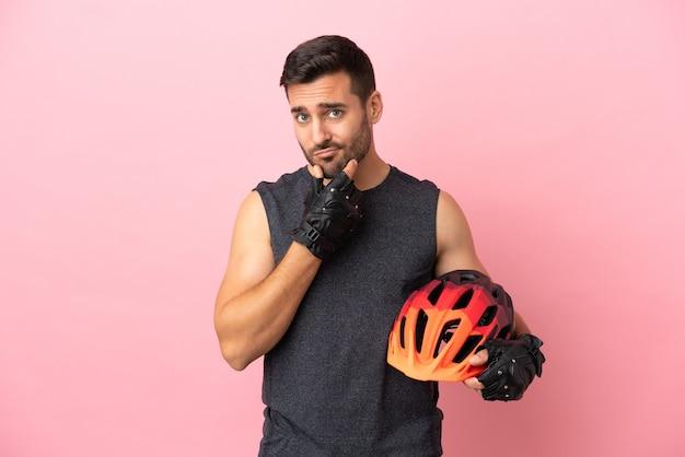 Молодой велосипедист человек изолирован на розовом фоне мышления