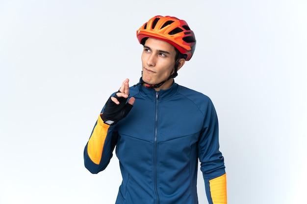 Молодой велосипедист изолирован на поверхности со скрещенными пальцами и желает всего наилучшего