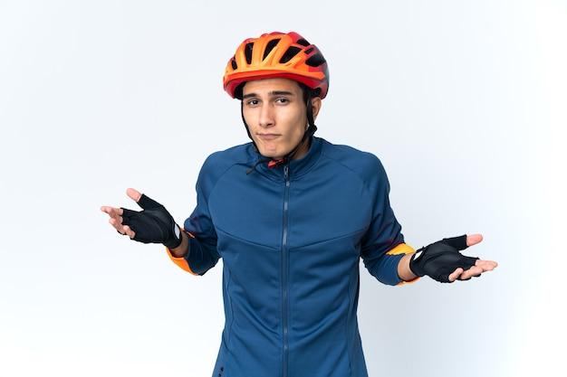 Молодой велосипедист человек изолирован на стене, сомневаясь, поднимая руки