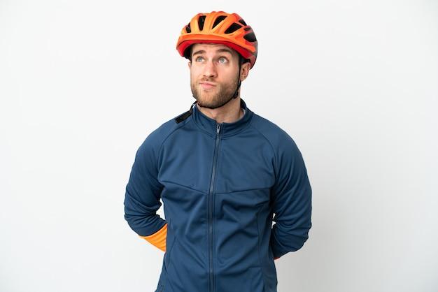 Молодой велосипедист человек изолирован на белом фоне и смотрит вверх