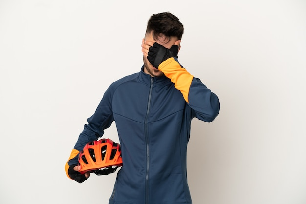 手で目を覆っている白い背景で隔離の若いサイクリストの男。何かを見たくない